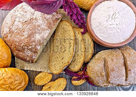 Bread, rolls and biscuits, flour of amaranth in a clay bowl, purple amaranth flower on the background of the wooden planks on top