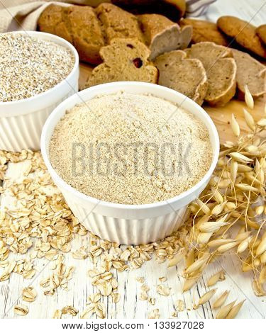 Flour oat and bran in two white bowls, oatmeal, oat stalks, bread and biscuits, cloth on a background of wooden boards