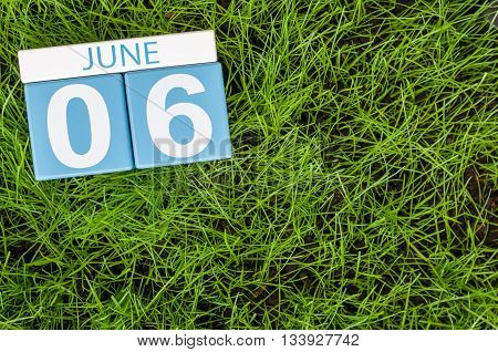 June 6th. Image of june 6 wooden color calendar on greengrass lawn background. Summer day, empty space for text.