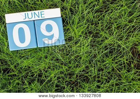 June 9th. Image of june 9 wooden color calendar on greengrass lawn background. Summer day, empty space for text.