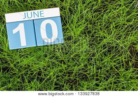 June 10th. Image of june 10 wooden color calendar on greengrass lawn background. Summer day, empty space for text.
