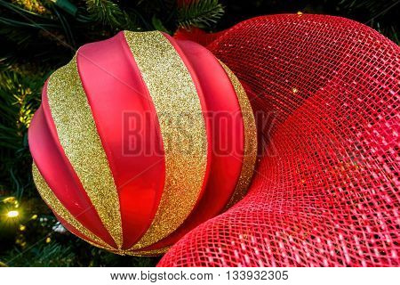 Christmas sphere or bauble next to red netting material. A closeup view. The tungsten lighting gives the image a warm feeling.