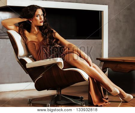 beauty young brunette woman sitting near fireplace at home, summer warm evening in interior, waiting to celebrate, lifestyle people concept