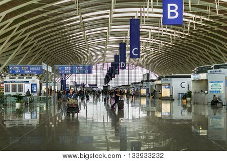 SHANGHAI, CHINA - MAY 2016: Pudong Airport interior and passengers in the departure terminal,  Shanghai, China. Pudong airport is the busiest international hub of mainland China, third busiest by cargo traffic in the world.