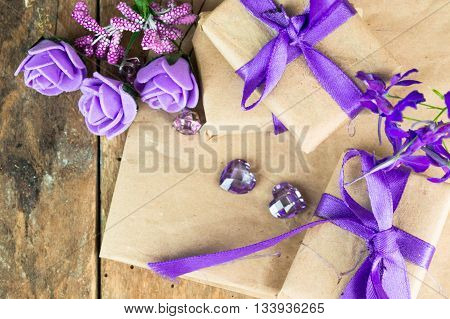 Wrapped gift boxes with presents and decorative flowers on aged wooden background. Place for text.