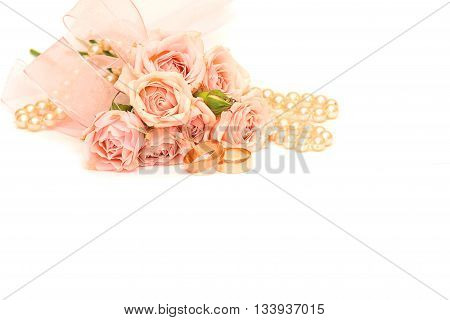 two golden rings pearls and delicate roses on white background