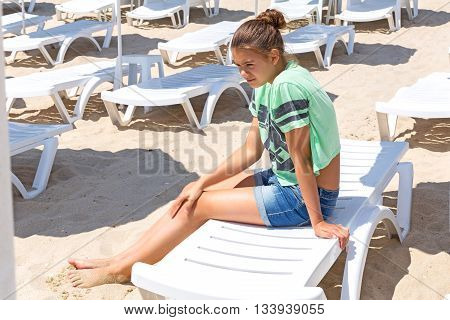 Teenage girl sitting on a lounger on the beach
