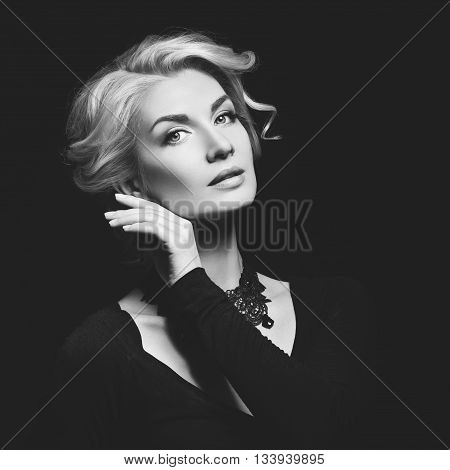 Beautiful blond young woman with natural makup and stylish hairdo. Beauty shot over dark grey background. Copy space. Square composition. Monochrome.