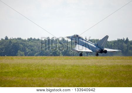 a military warplane lands on an airfield