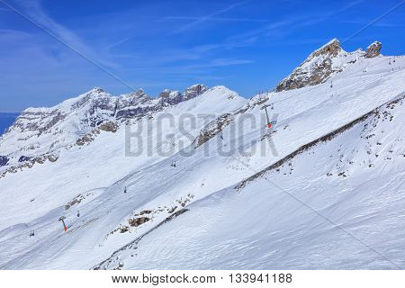 Alps, view from Mt. Titlis in Switzerland in the beginning of spring. Titlis is a mountain located on the border between the Swiss cantons of Obwalden and Bern, mainly accessed from the town of Engelberg on the north side.