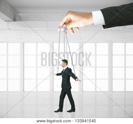 Hand manipulating businessman puppet on ropes in white brick interior. Concept of control