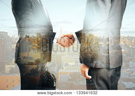 Businesspeople shaking hands on city background. Double exposure