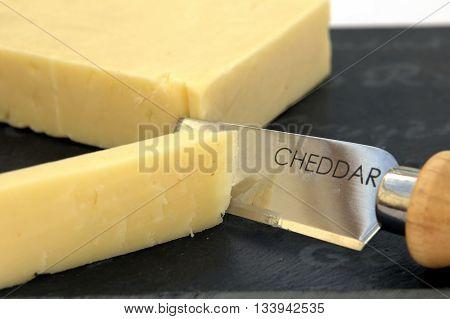 Fresh Cut Cheddar Cheese On A Slate Board