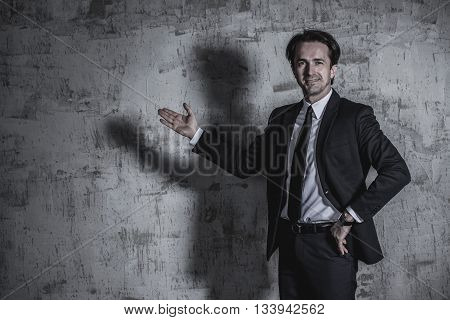 Portrait of a businessman in suit showing to empty space over concrete wall background
