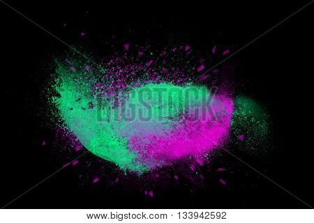 Freeze motion of colorful powder paint exploding isolated on black dark background. Abstract design of color dust cloud. Particles explosion screen saver wallpaper brush