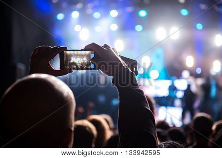 Man capturing festival memories with mobile phone.
