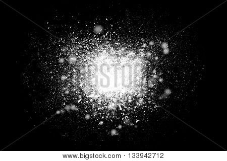 Freeze motion of white powder exploding isolated on black dark background. Abstract design of dust cloud. Particles explosion screen saver wallpaper with copy space.