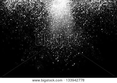 Freeze motion of white powder coming down isolated on black dark background. Abstract design of falling dust cloud. Particles cloud screen saver wallpaper with copy space. Rain snow fall concept