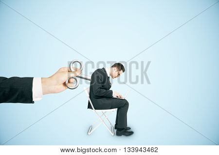 Hand activating businessman with a wind-up key on his back on blue background. Concept of control