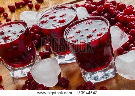 Cold cranberry drink in glasses, cranberries and pieces of ice on wooden background.