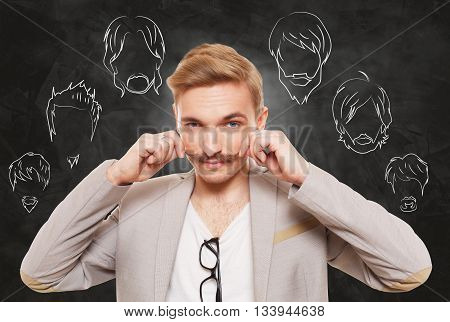 Man choose facial hair style, beard or mustache. Barber shop haircuts choice. Male fashion, various hair styles drawings at blackboard. Stylish young guy think of changing hairstyle. Man portrait