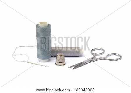 Needle, thimble, scissors, thread and knob isolated on white background