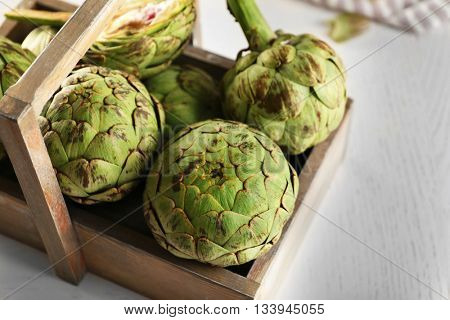 Artichokes in wooden container on light background