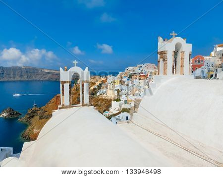 Oia, Greece - June 10, 2015: Santorini - The beautiful white bell tower on the sea in the background. Beautiful sea view on Santorini island, Oia, Greece.