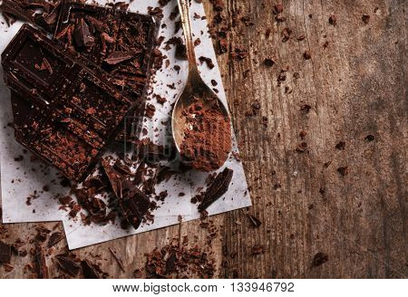Spoon with cocoa powder and chocolate bar pieces  on wooden background