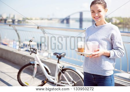 Have a drink. Cheerful pretty young woman holding some beverages while standing in front of the bicycle with a river on the background