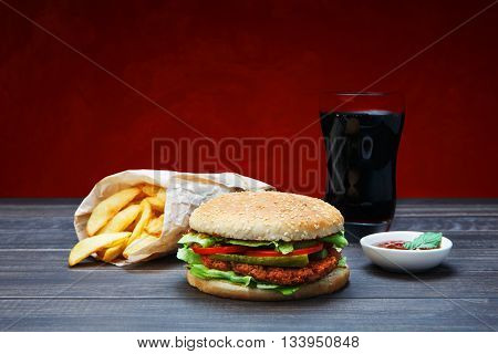 Fast food. Hamburger, potato fries, cola drink. Takeaway food. Wrapped French fries, Cola glass, tomato sauce, double cheese hamburger at rustic blue wood and red background.