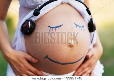 Prenatal education. Pregnant woman belly closeup with smiling funny face drawing listening to the music outdoors. Earphones at woman's belly. Happy pregnancy, fun, creativity.