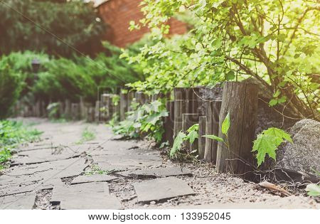 Beautiful landscape design, garden path tiles closeup with wooden log fence from roundwood, evergreen bushes and shrubs in sunlight. Modern landscaping. Summer garden or park design.
