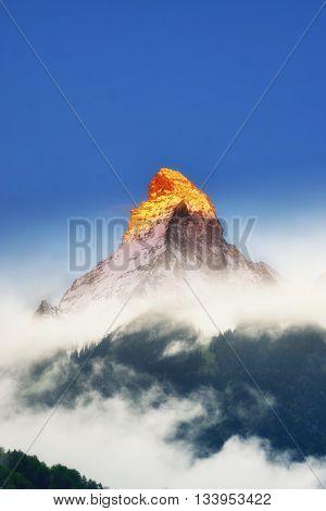 Golden Sunlight on top of Matterhorn mountain with mist in early morning Zermatt Switzerland
