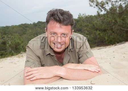 Man On Beach Lying In Sand Looking To Side Smiling Happy Wearing A Green Shirt.