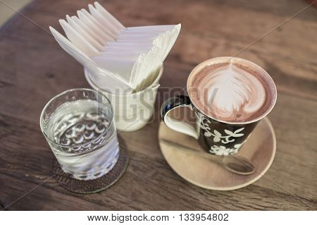 hot coffee with tissue paper coffee on wooden table coffee and glass of water coffee near red sofa