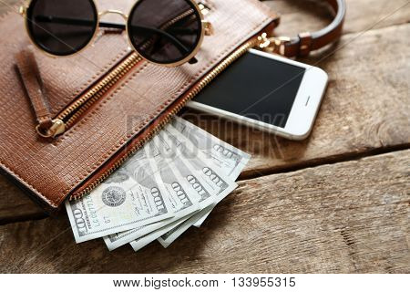 Leather purse with mobile phone, glasses and dollar banknotes on wooden table