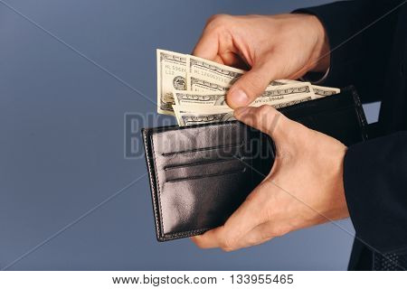Man getting dollar banknotes out of purse on grey background