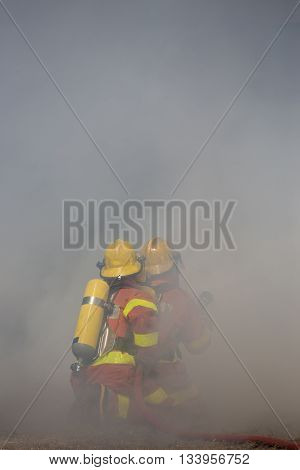 two firefighters is working surround with smoke