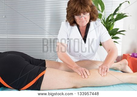 Physiotherapist massaging the leg of male patient in a physio room.