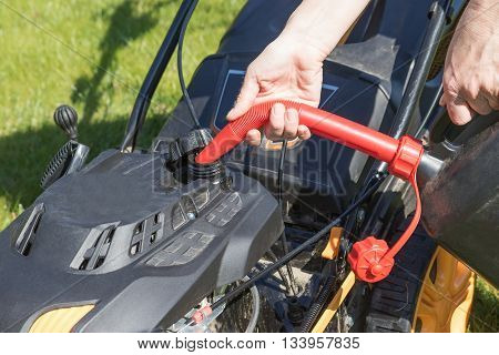 Pouring gasoline into the tank of diesel lawn mower.