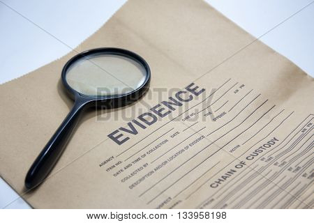 magnifying glass with evidence brown paper bag