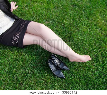 Young business woman took her high heels off to rest the feet and sits on a grass in park