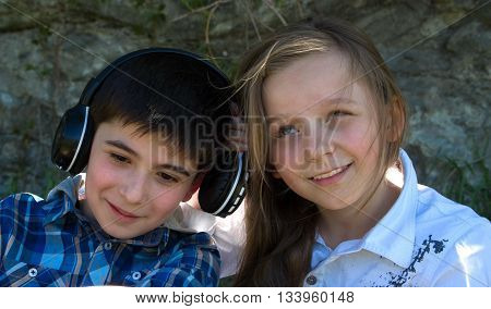 Little boy listens music with earphones and litle girl tryes to hear what does he leaten to