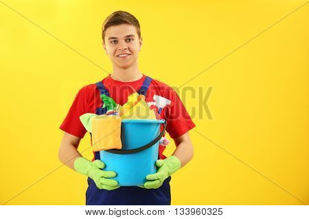 Man holding plastic bucket with brushes, gloves and detergents on yellow background