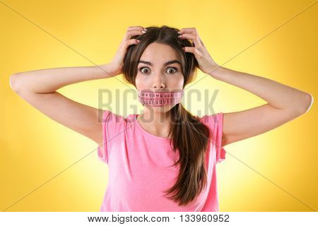 Woman with locked mouth for diet on yellow background