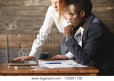 Two Business Partners Looking At Laptop Screen Indoors. African Coworker Sitting Seriously With Chin