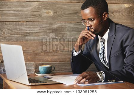 Serious African American Businessman Looking At Laptop Screen And Thinking Upon Problem While Sittin