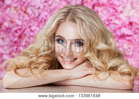 Portrait of cute young girl with beautiful makeup. Blond hair wavy curls. Beauty clean skin . Photographed in studio on a floral background . Light Tone .