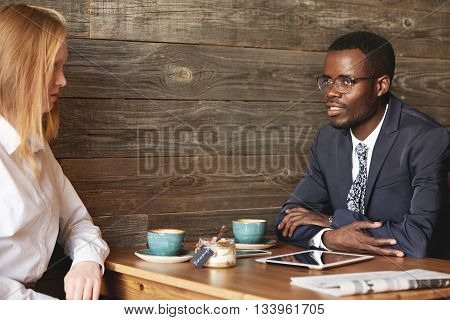 Young African Entrepreneur In Round Glasses Sitting At Business Lunch In A Café And Drinking Co